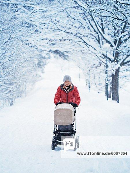 Smiling mother walking with pram at winter landscape