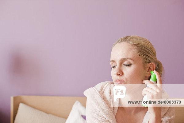Woman applying spray into ear