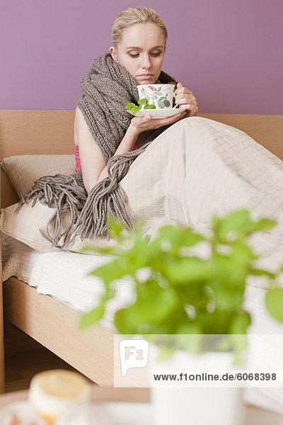 Sick woman drinking herbal tea
