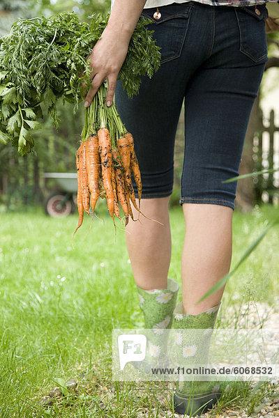 Rückseite des Frau mit frischen Karotten
