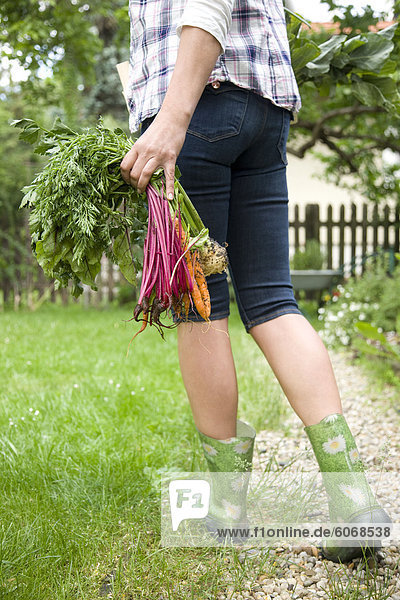 Woman with fresh vegetables in garden