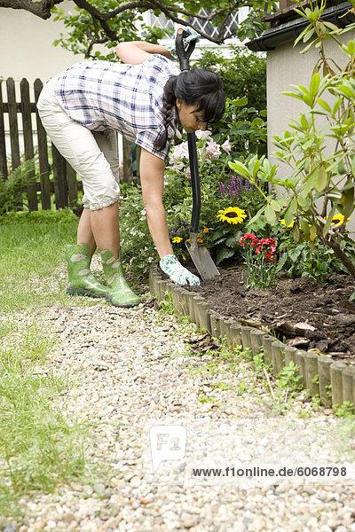 Frau sucht am Boden im Garten
