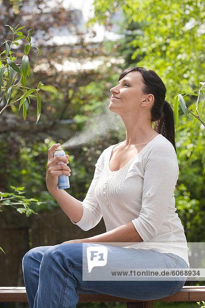 Woman spraying mist on face