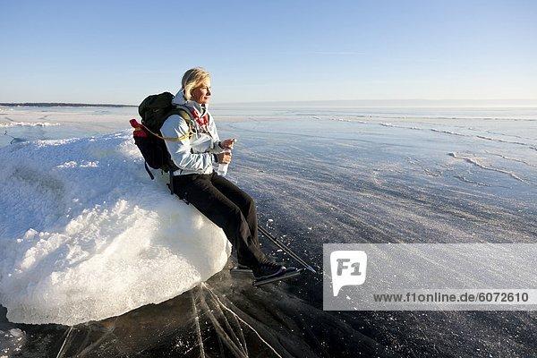 Frau sitzt auf dem Eis