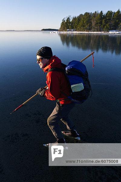 Man Eislaufen am zugefrorenen See