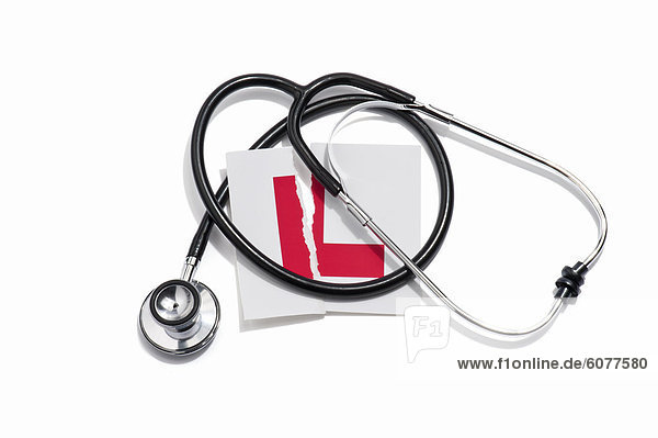 A doctors stethoscope and a torn learners permit sticker
