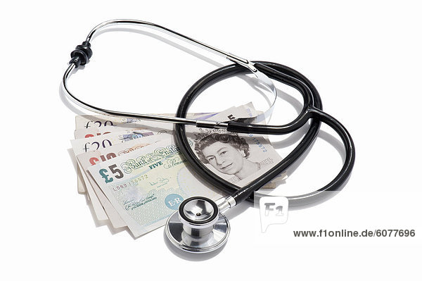 A doctors stethoscope and British pound notes