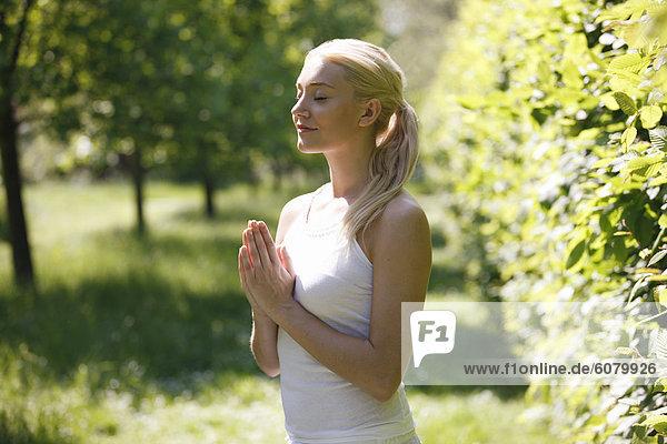 Eine junge Frau praktizieren Yoga außen  Hände im Gebet Standpunkt