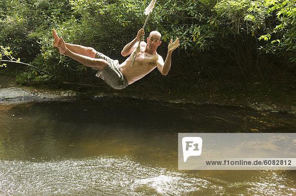 schaukeln  schaukelnd  schaukelt  schwingen  schwingt schwingend  Mann  Seil  Tau  Wald  North Carolina  Schaukel