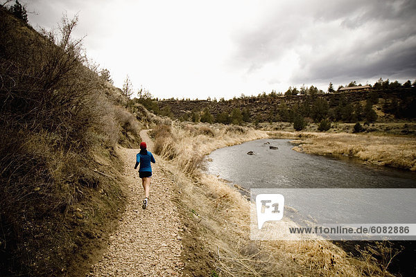 A woman jogging on a dirt trail in Oregon.