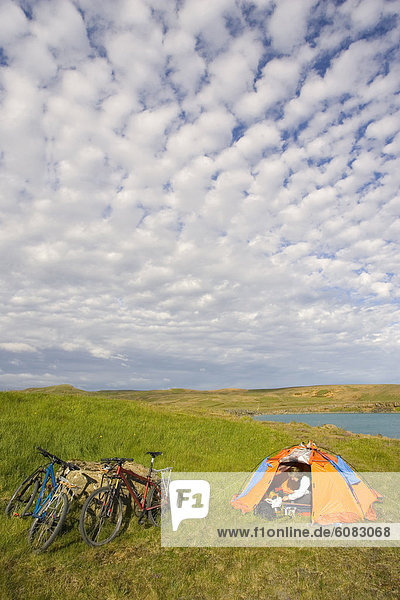 A young woman resting in a tent after mountain biking along the Reykjavik Peninsula  Iceland.