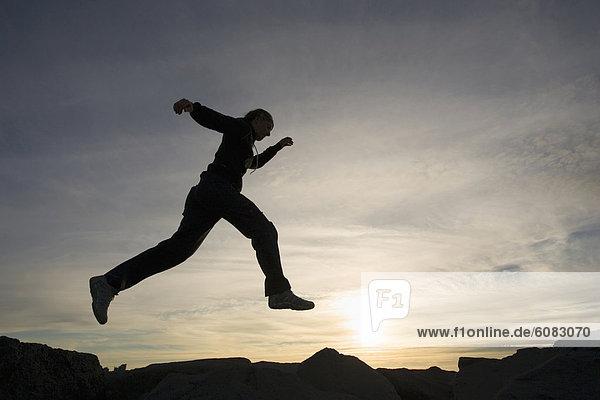 Reykjavik  Hauptstadt  Felsbrocken  Gegenlicht  Frau  Sonnenuntergang  springen  jung  Island