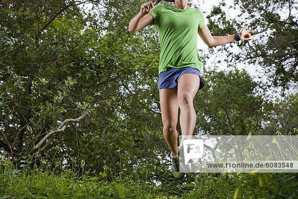 View from below of a woman trail running through a green meadow in the woods.