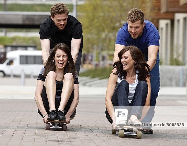 Frau  Mann  lachen  schieben  Weg  Großstadt  2  jung  Skateboard