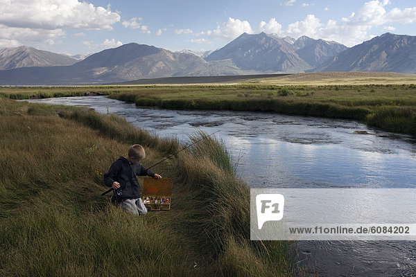 A boy looks through his tackle box while fishing for trout in the Eastern Sierra Mountains.