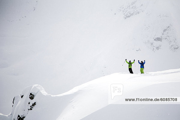 Two male skiers raise their hands over their heads in excitement on a snowy peak in Alaska.