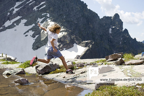 A young girl sails over a pool of water as she hops from rock to rock in Glacier National Park  Montana.