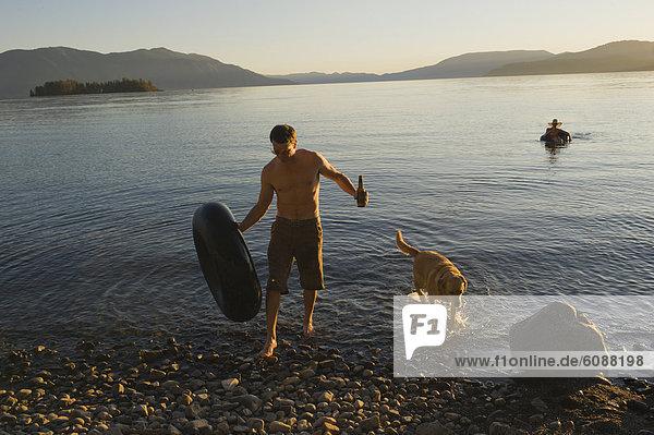 Mann  ankommen  Hund  See  jung  schwimmen  Küste