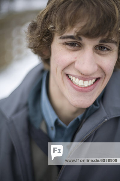 Portrait of young man smiling outside in winter.