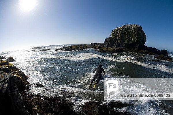 Felsbrocken  Mann  Ozean  Surfboard  Wellenreiten  surfen  Tauchanzug  Kleidung  springen  Chile
