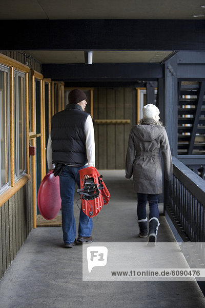 A man and woman walk a balcony with a sled and snowshoes  ready to enjoy the mountain snow.