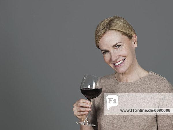 Reife Frau mit Weinglas  lächelnd  Portrait