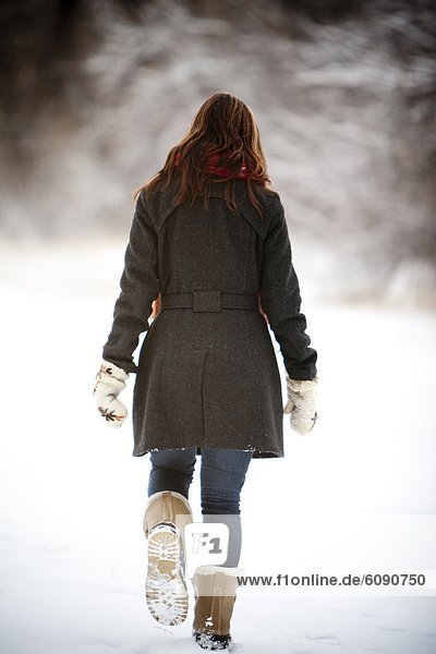 A woman walks through a snowy field on an overcast winter day  in Fort Collins  Colorado.