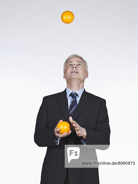 Reife Männer jonglieren mit Orangen