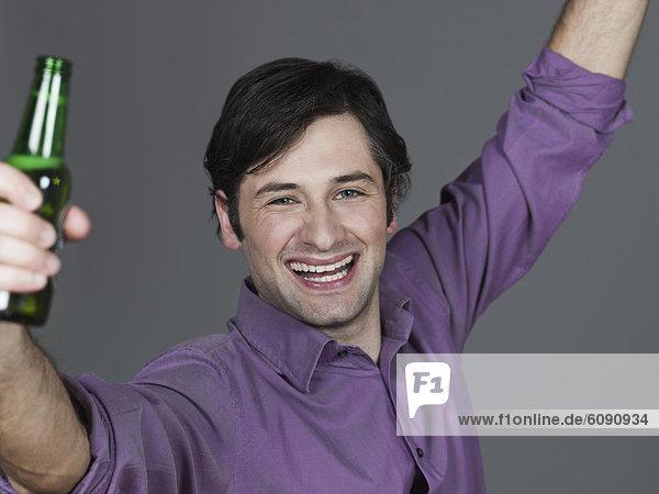 Junger Mann mit Bierflasche  lächelnd  Portrait