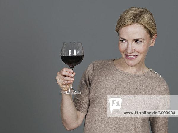 Reife Frau mit Weinglas  lächelnd