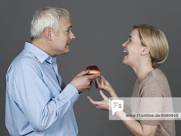 Erwachsenes Paar mit Kuchen  lächelnd