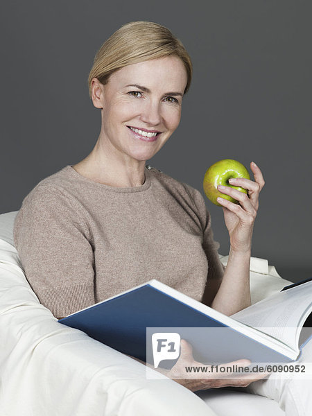 Reife Frau mit Buch und Apfel  lächelnd  Portrait