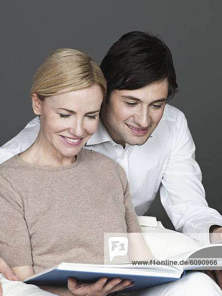 Mann und Frau lesen Buch  lächelnd