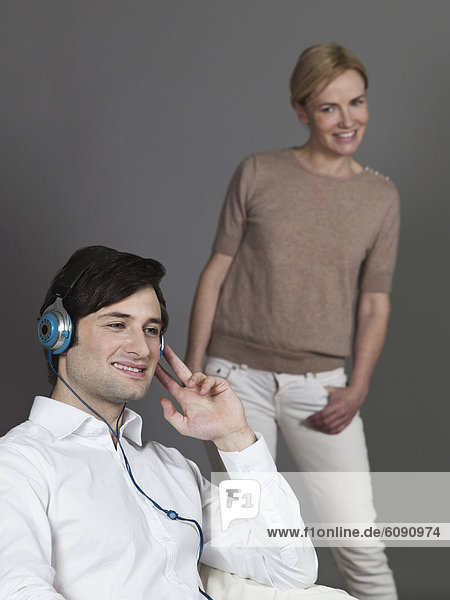 Man with earphones  woman looking at him