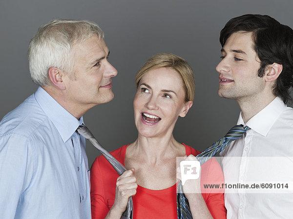 Frau zieht die Krawatte der Männer  lächelnd