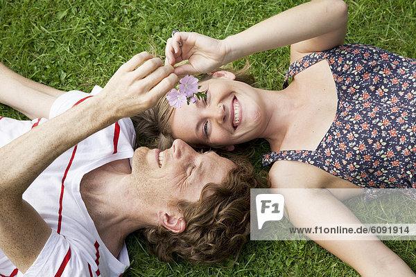Mann und Frau auf Gras liegend im Schrebergarten