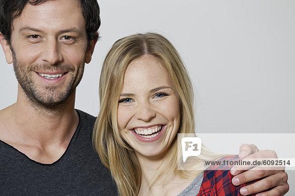 Paar lächelnd vor weißem Hintergrund  Portrait