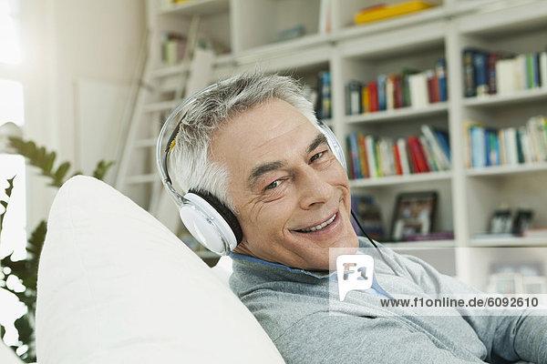 Senior Mann mit Kopfhörer auf Couch  Portrait