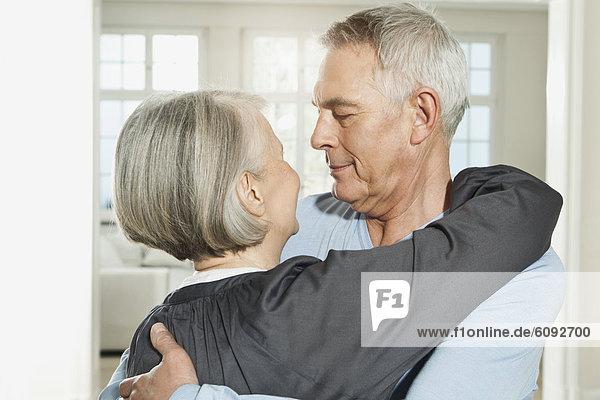 Deutschland  Berlin  Seniorenpaar umarmend  lächelnd