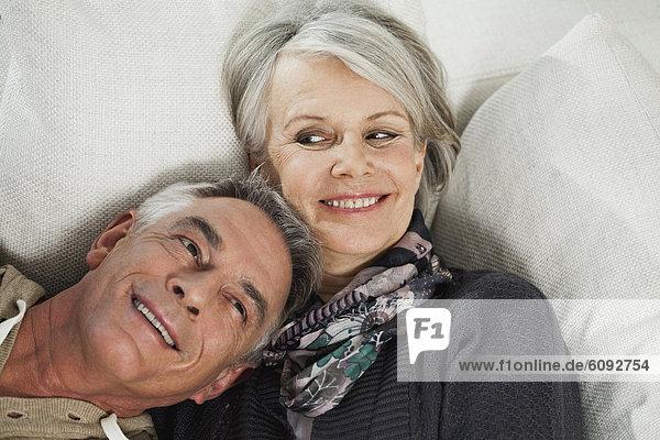 Deutschland  Berlin  Seniorenpaar auf Couch liegend  lächelnd