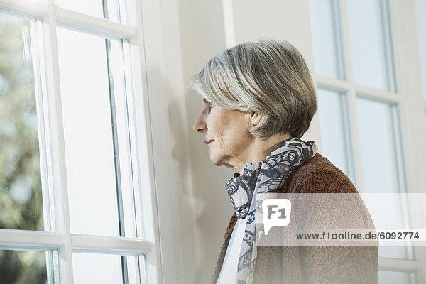 Seniorin schaut durchs Fenster