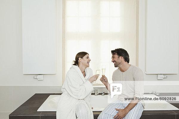 Deutschland  Berlin  reifes Paar auf der Badewanne mit Sekt