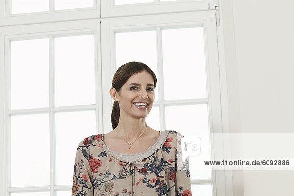 Reife Frau lächelnd vor dem Fenster  Porträt