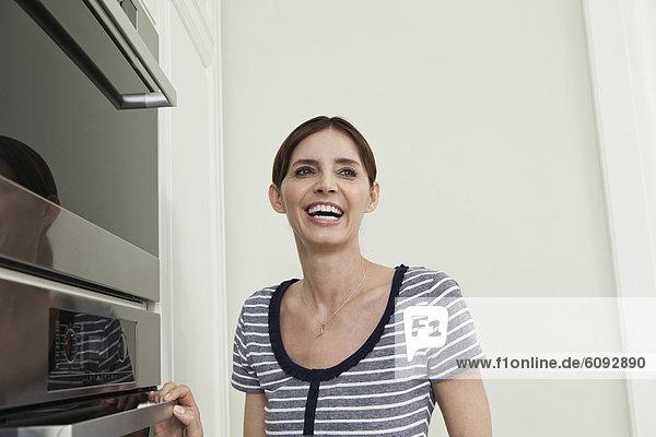 Reife Frau  die am Ofen in der Küche lächelnd schaut