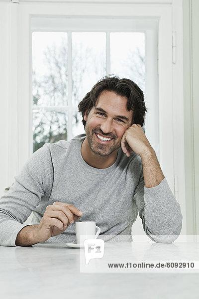 Erwachsener Mann mit Kaffeetasse  lächelnd  Portrait