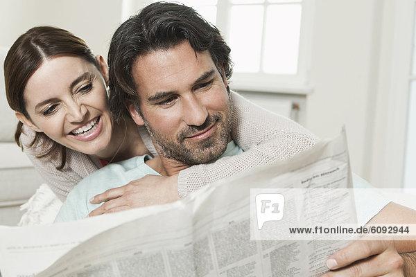 Deutschland  Berlin  reifes Paar beim Zeitung lesen  lächelnd