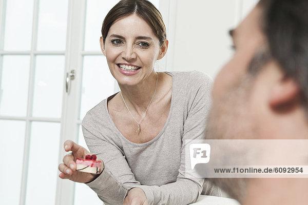 Mann schaut Frau an  die Kuchen hält