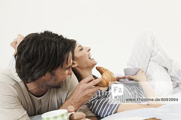 Deutschland  Berlin  Ehepaar beim Frühstücken im Bett
