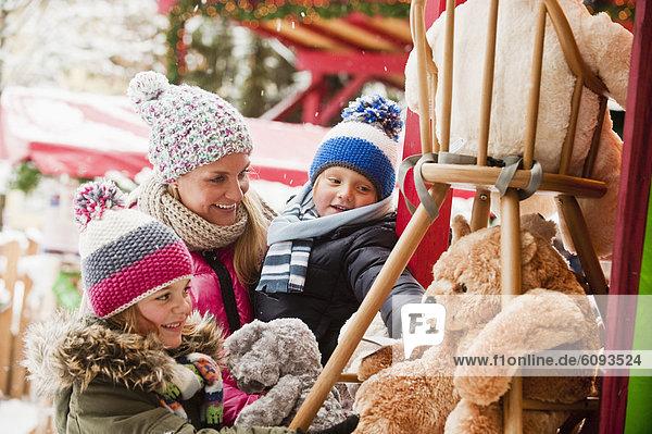 Austria  Salzburg  Mother with children at christmas market  smiling
