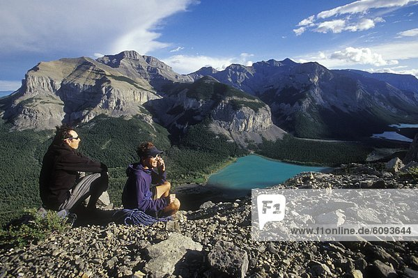 Two climbers stay in touch by talking on a cell phone in the mountains.